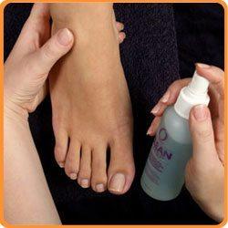 нанесение антисептического спрея на ноги