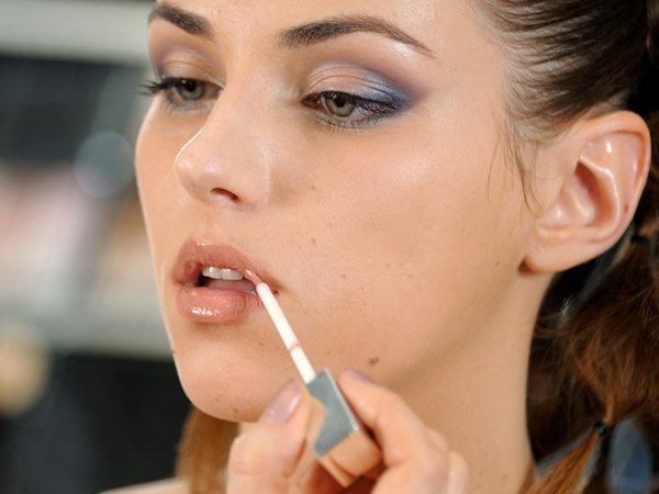 девушка поправляет блеск на губах