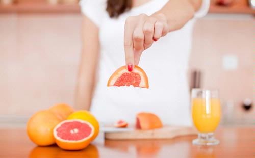 долька цитрусового фрукта в руке